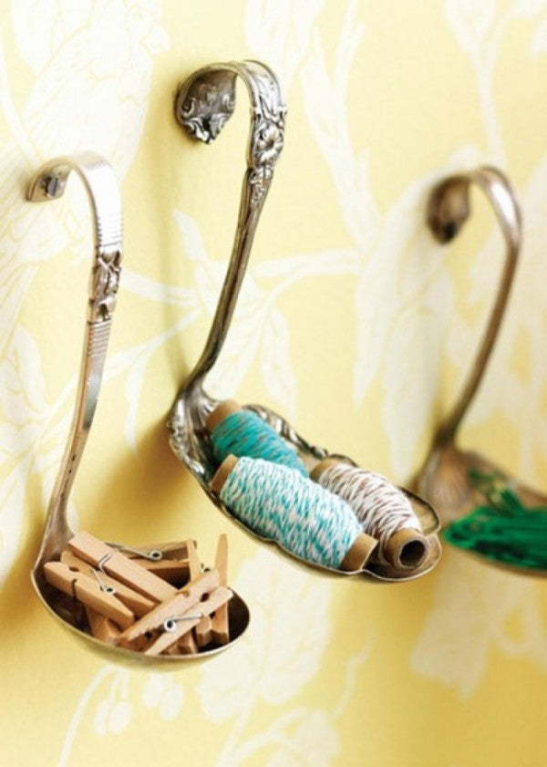 Silver spoons attached to a yellow wall and used to store pegs, string and paperclips