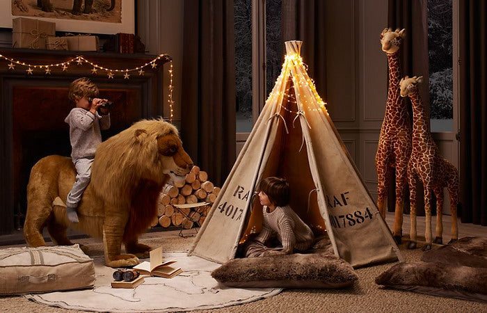 Safari themed magical kids bedroom with stuffed lion, giraffes and tent