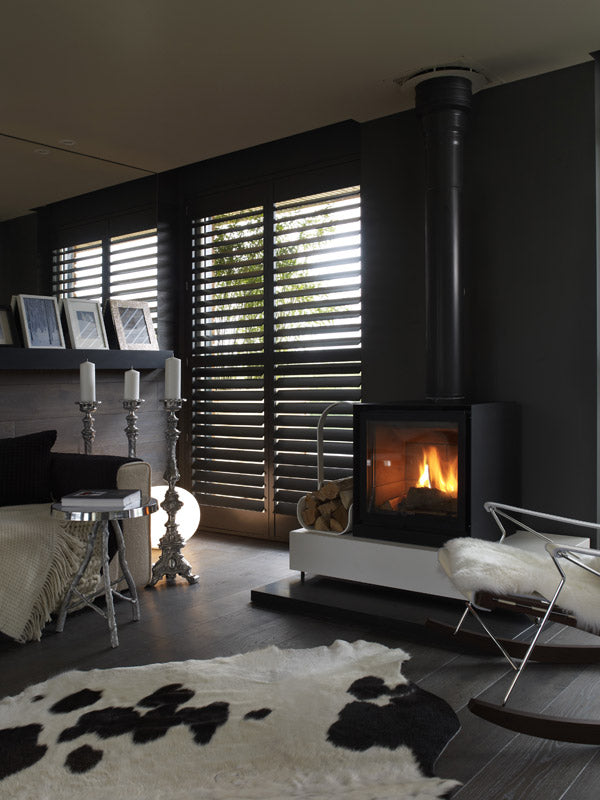 Luxury black interior with roaring log fire, cream sofa and black and white faux fur rug