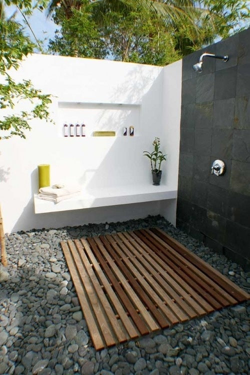 Outdoor courtyard shower, with black tiled wall, pebbled floor and wooden slatting under the shower