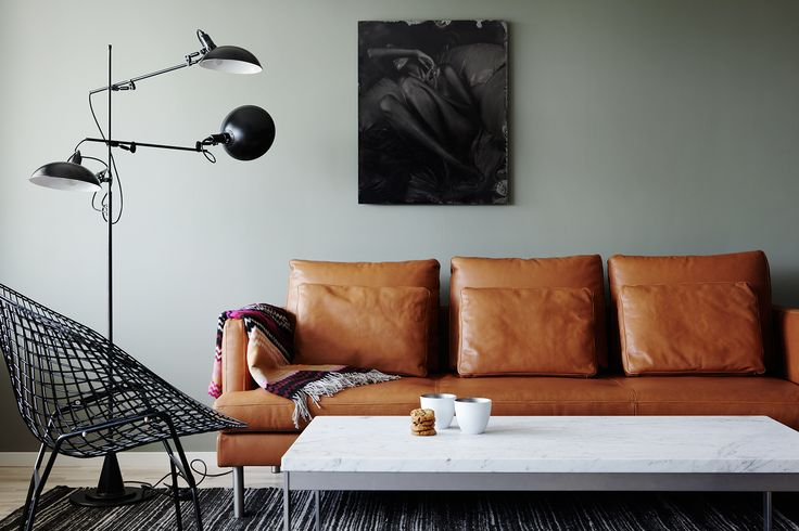 Brown leather sofa in a light grey living room, with funky hinged black floor lamp