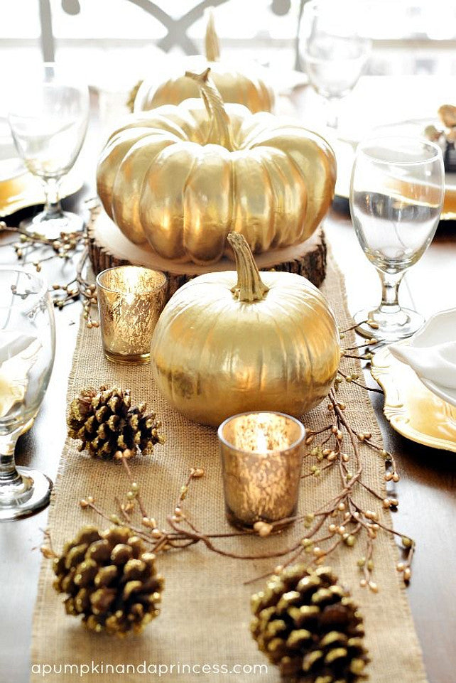 Gold Thanksgiving table setting with gold pumpkins, glasses and pine cones