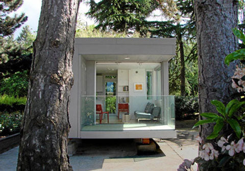 Small square purpose built pod home, surrounded by trees