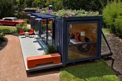 Small modular home in dark blue made from an old storage container