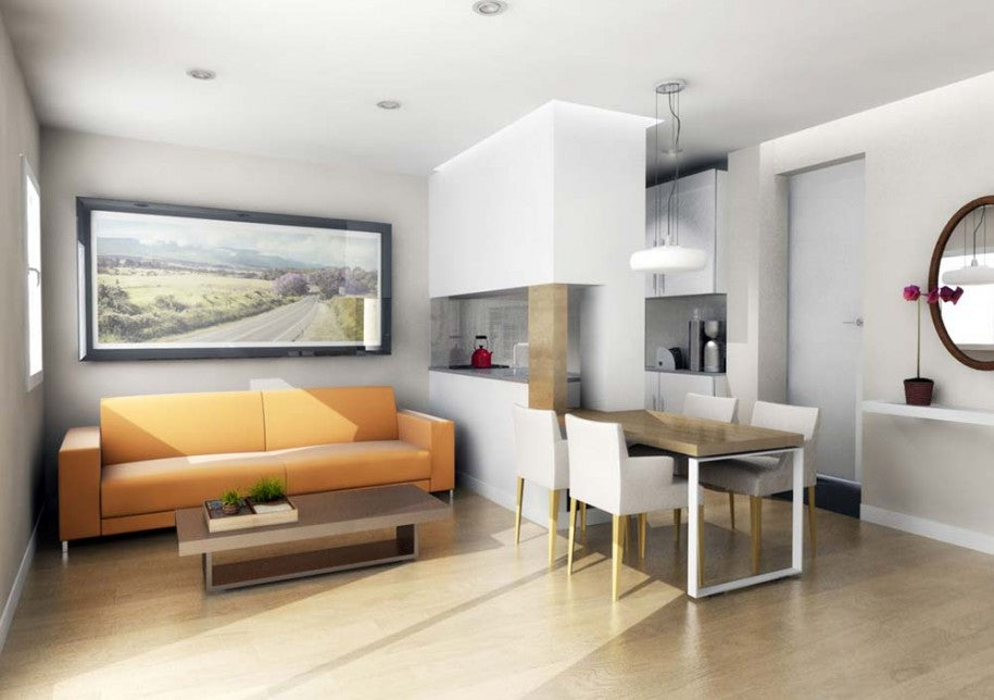 White kitchen and living space, with orange sofa, and well utilised narrow kitchen and dining table space