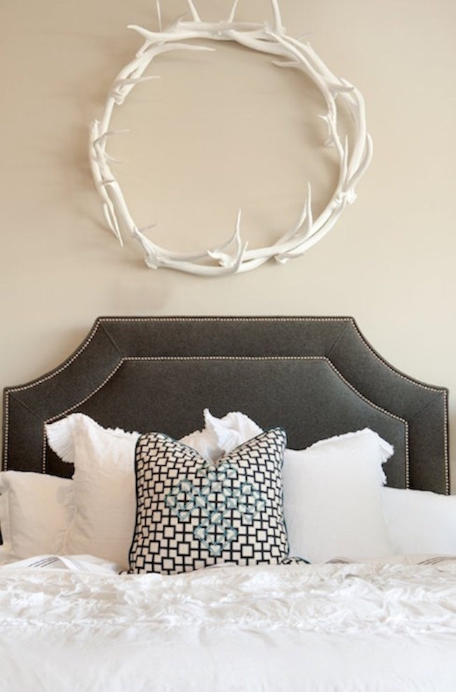 Round white decorative antlers over a bed