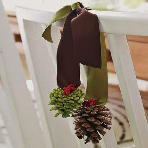 Brown and green ribbon and pine cones, used to decorate white wooden chairs