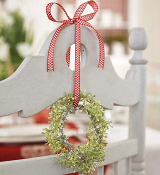 Red and white ribbon and light green plant garland, used to decorate white dining chairs