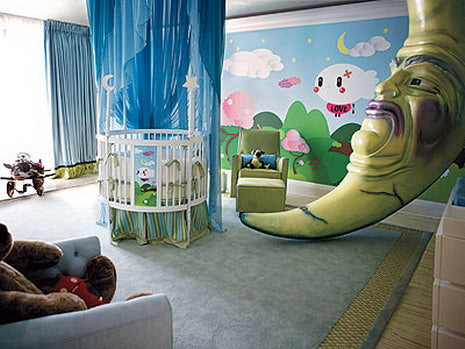 Baby's nursery with round cot surrounded by blue voile canopy and giant grumpy moon figure filling the room