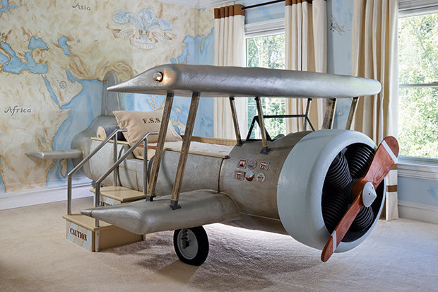 Childrens bed that looks like an explorers aeroplane, with a painted world map on the wall