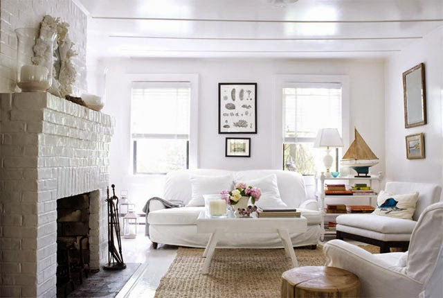 White living room with cream brick fire place and white sofas and white chairs