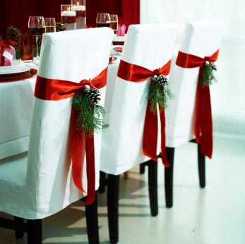 Dining chairs with white covers and red ribbon decorated with pine cones