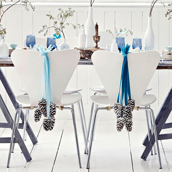 Dining table and white chairs with blue ribbon and pine cone festive decorations