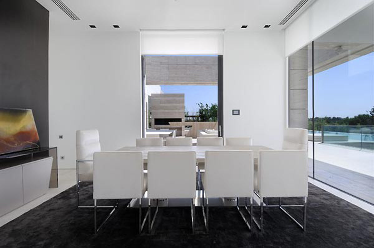 Black and white dining room with two large floor to ceiling windows overlooking a balcony