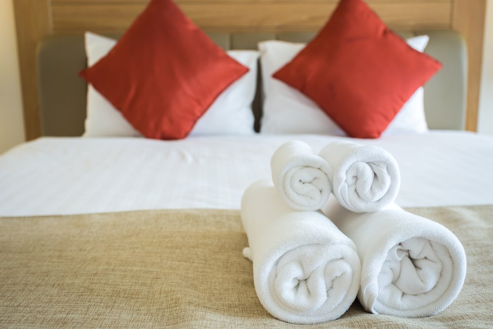 Guest room with folded towels on the bed