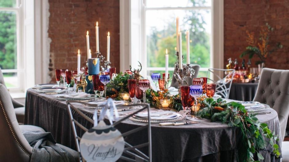 Lovely festive dining room table, with grey tablecloth and candles and centrepiece