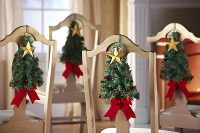 Dining chairs with small Christmas tree garland, gold star and red ribbon