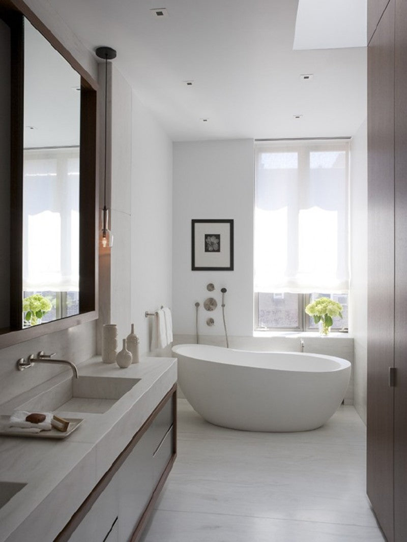 White and beige bathroom with stylish curved bath tub and large window