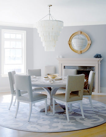 White and light blue round dining room with cascading white light fixture
