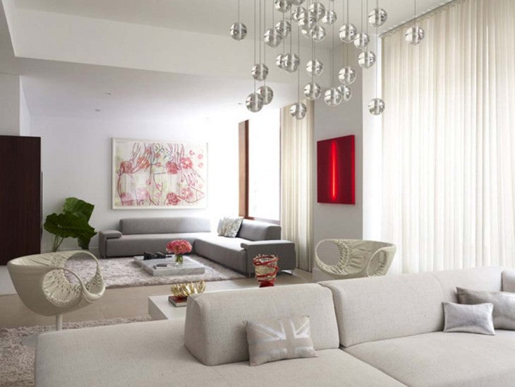 Modern white living room with one cream sofa and one grey sofa, plus light feature with clear glass orbs