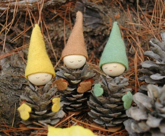 Three pine cone people with little felt hats, gloves and round little face