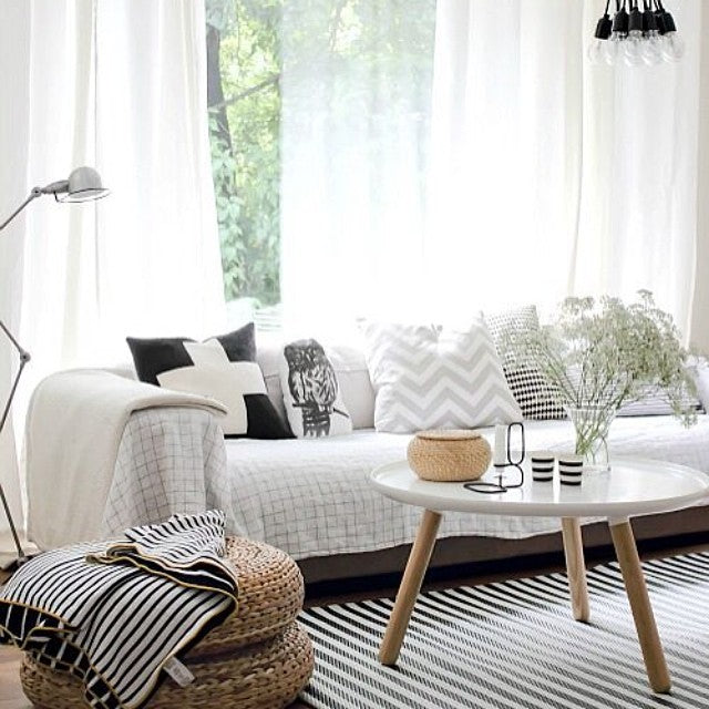 White throw on sofa in front of large window with large white voiles