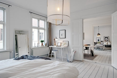 White bedroom with white bedding and large round cream fabric lamp shade