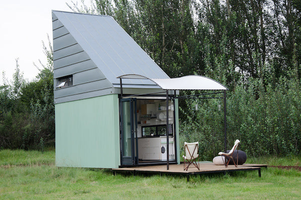Tiny cube shaped eco-home in light green with a grey triangular roof