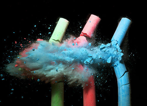 Slow motion image of three pieces of chalk exploding and chalk dust flying to the left
