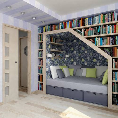 Grey, light green and cream reading nook under a wall of bookshelves