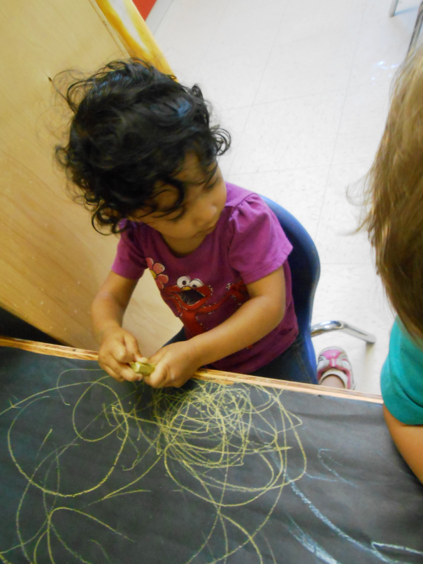 Child drawing on a chalkboard with yellow chalk