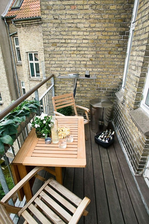 Small apartment balcony with wooden garden furniture and chilled beer