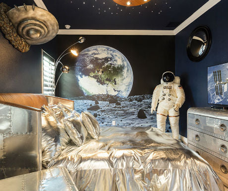 Space themed bedroom with astronaut suit in the corner and wall decal of the moon and a view of the Earth