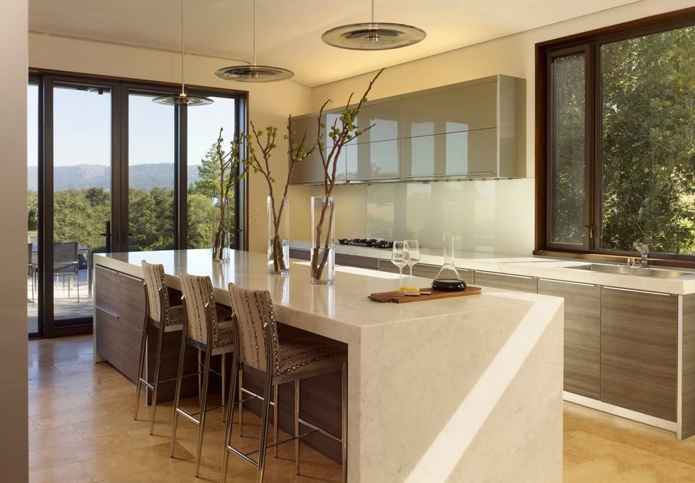 Very modern and stylish kitchen space with clean reflective surfaces and french doors