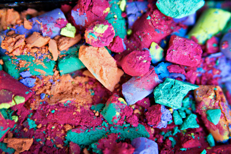 A closeup of different pieces of chalk and coloured chalk dust