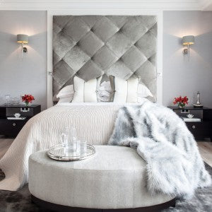 Fabric Covered Headbaord, white Bedding And Soft Grey Ottoman At The Foot Of The Bed