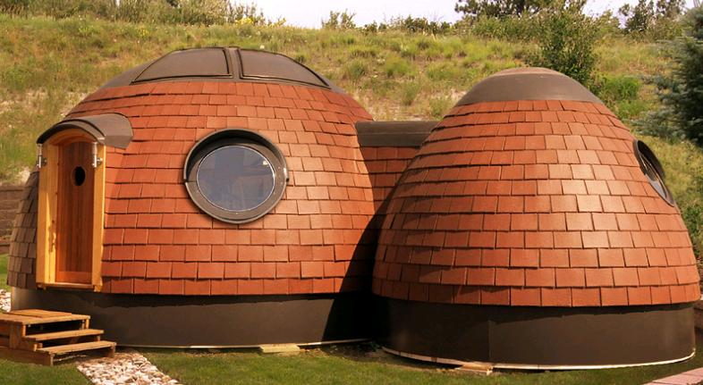 Tiny house pods covered in red tiles, they resemble owls