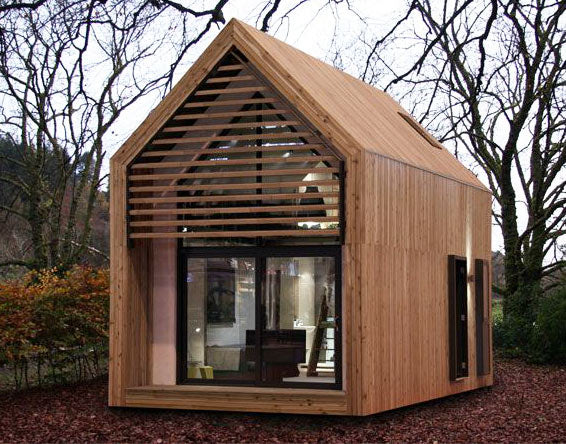 Garden studio room in a traditional house shape made from wood, with two floors and big glass front