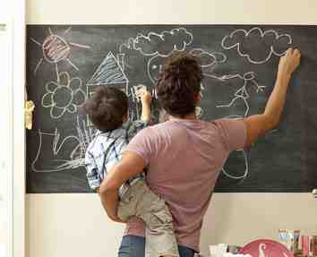 Parent and child drawing on a chalk board