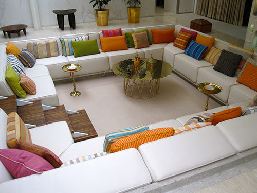 Conversational area with four cream corner sofa making a square seating area, covered in different coloured cushions