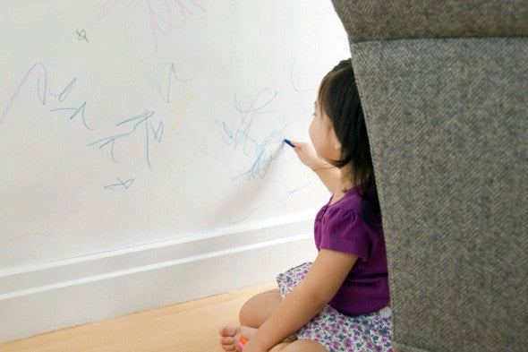 Toddler scribbling on a wall with blue crayon