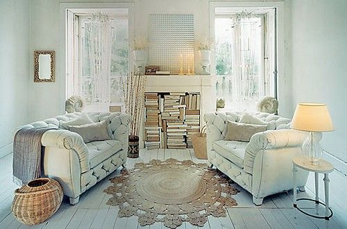 Light blue living room with white leather sofas and cream fireplace filled with books