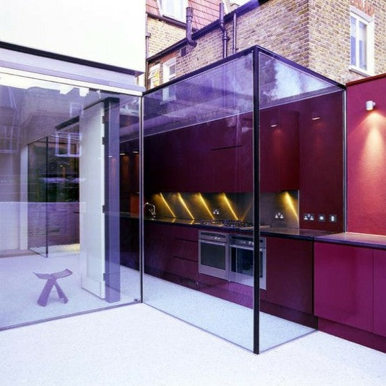 Kitchen extension made from large glass panels, allowing the kitchen to look as if it's part of the garden