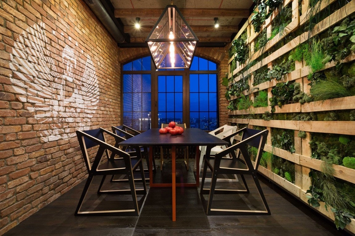 An urban style dining room with exposed brick on one wall and floor to ceiling pallets containing greenery on the opposing wall
