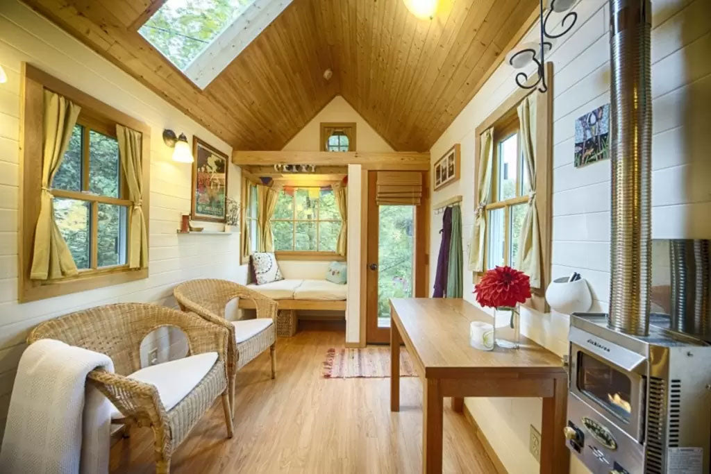 Wooden eco home with wicker two seater chairs facing a table
