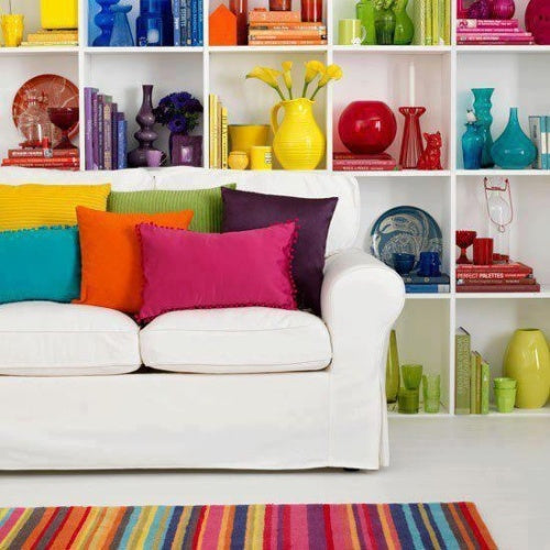 Lots of bright objects in a white wall shelf unit, with coloured cushions on a white sofa