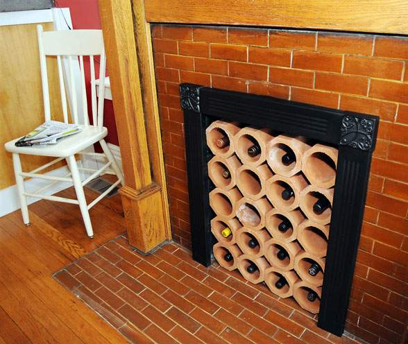 Traditional ceramic tiles covering a fireplace, with wine rack blocking up the hearth