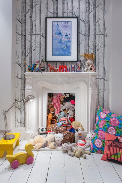 White and grey kids room with white fireplace and hearth stuffed with teddies and stuffed toys
