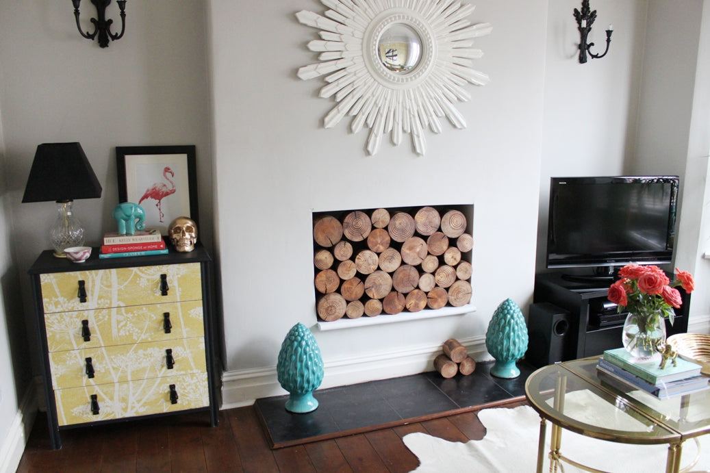 White living room with fireplace filled with logs, with no mantle piece present