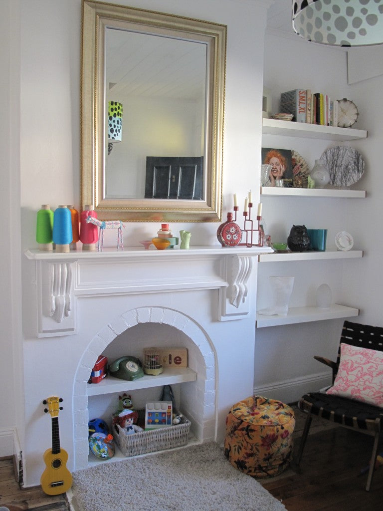 White room with white fireplace and mantle piece shelf, plus shelves inside the hearth